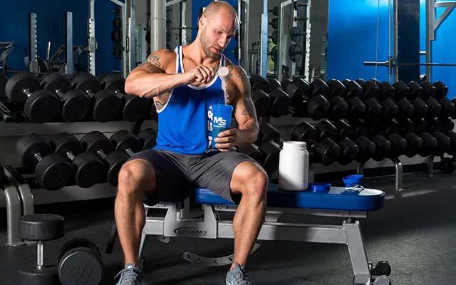 Бодибилдер делает протеиновый коктель во время тренировки.